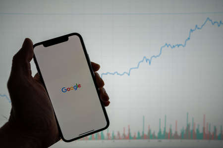 Google logo on phone with white financial stock chart with price rising upward positive in background