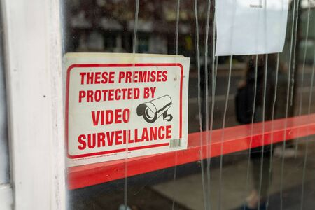 These premises are protected by video surveillance and camera sign outside of store window Banco de Imagens