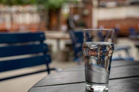 Full glass of water sitting on wooden picnic table in a restaurant