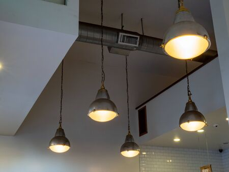 Flood lights hanging from ceiling with ventilation duct in a clean building 免版税图像