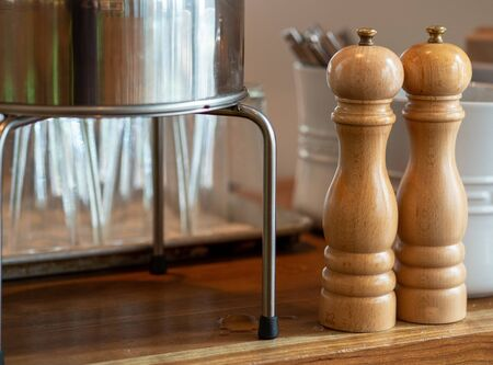 Wooden hand crank salt and pepper shaker on table near utensils and glasses Archivio Fotografico