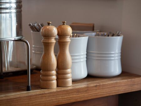 Wooden hand crank salt and pepper shaker on table with utensils in some ceramic pots 免版税图像