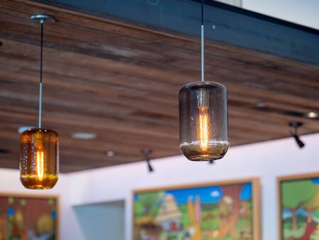 Filament light bulbs hanging high on wooden ceiling inside building Imagens - 143773156
