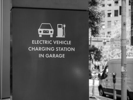 Electric vehicle charging station in garage symbol and sign posted outside on the street Imagens