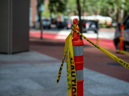 Yellow caution tape tied to orange safety cone positioned on the street