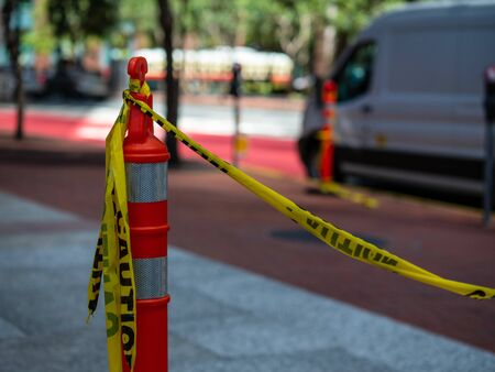 Yellow caution tape tied to orange safety cone on sidewalk with a van in background Stock fotó