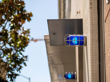 Blue caution safety lights affixed to a building outside and positioned high