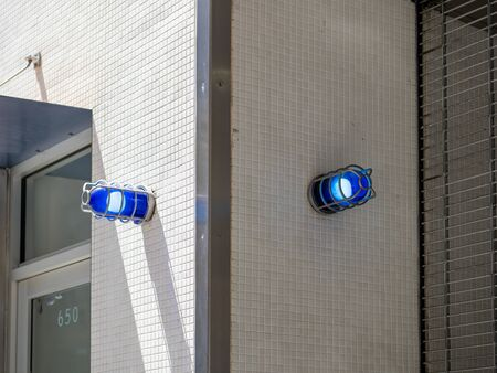 Two blue caution safety lights on corner of a building outside