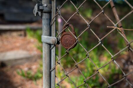 Chain link fence with rusted padlock opening in a nature area