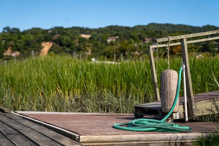 Buoy and hose sitting on dock in a grasslands area Imagens