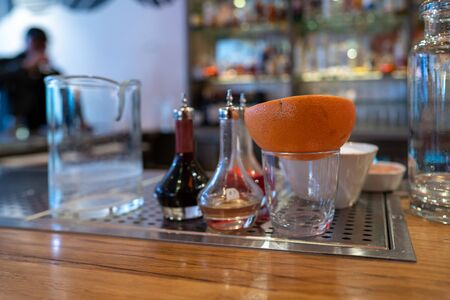 Half an orange sitting in a glass next to various cocktail and drink tools on a bar counter Imagens