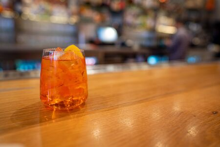Full orange spritz cocktail drink sitting on bar counter