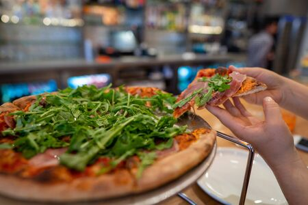 Woman grabbing slice of pizza with some arugula greens on top Imagens