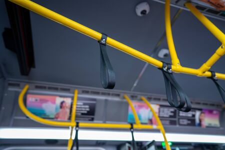 Suspended safety rail wrist straps on a public transportation bus 免版税图像