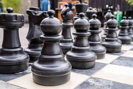 Close up of human sized black chess pieces with pawns in front