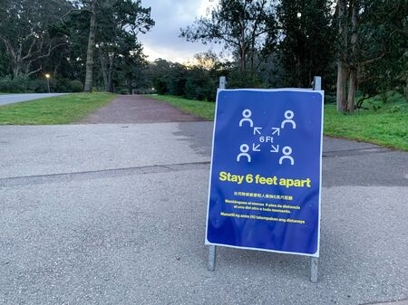 Coronavirus COVID-19 social distancing signboard in public park in front of dirt walking path trail Banco de Imagens