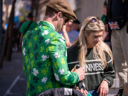 Man in shamrock green jacket with women in Guinness sweater celebrating St Patrick s Day