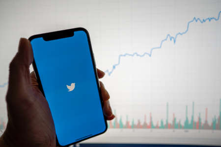 Twitter app and logo on phone with white financial stock chart with price rising upward positive in background