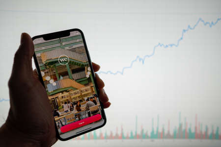 WeWork app and logo on phone with white financial stock chart with price rising upward positive in background