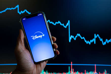 Disney Plus Disney app held against a dark stock trading chart going down in value