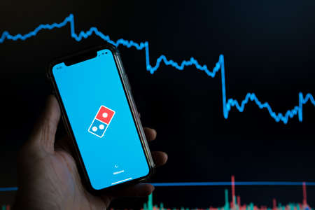 Dominos pizza mobile delivery app held against a dark stock trading chart going down in value