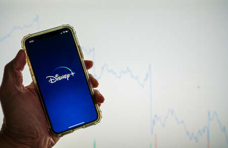 Disney Plus Disney mobile app held against a white stock market chart going down in value