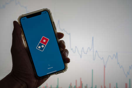 Domino s pizza mobile app held against a white stock trading chart going down in value