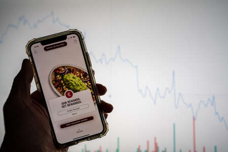 Chipotle mobile app on iPhone in front of white stock market chart with graph going down in value