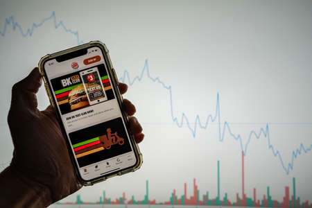 Burger King mobile app with deals on iPhone in front of white stock market chart with graph going down in value Sajtókép
