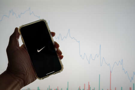Nike mobile app logo on iPhone in front of white stock market chart with graph going down in value