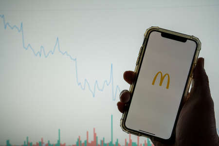 McDonald s mobile app logo on iPhone in front of white stock market chart with graph going down in value
