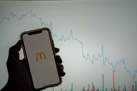 McDonald s mobile app logo on iPhone in front of white stock market chart with graph going down in value to the right