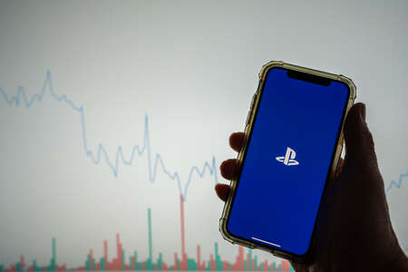 Sony Playstation mobile app logo on iPhone in front of white stock chart