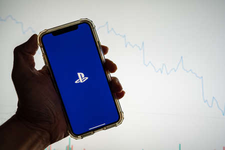 Sony Playstation mobile app logo on iPhone in front of white stock market chart with graph going down in value