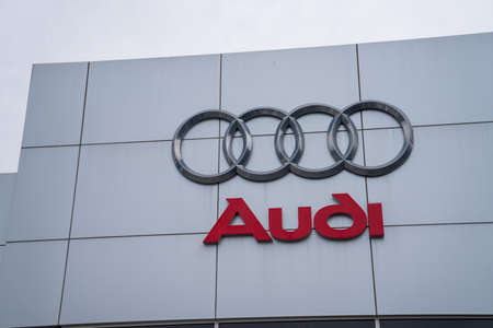 Audi automobile car logo and sign outside entrance of dealership