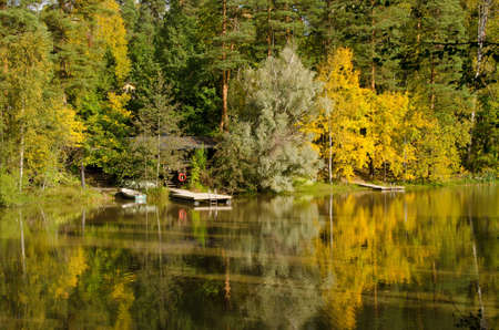 suomi: A small pontoon on a river with the reflection of trees on the river