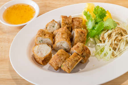 Fried Chicken meat filled in bean curd in a white dish on wooden table background