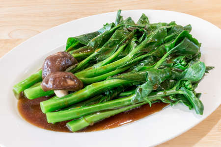 Stir-fried Chinese broccoli or Chinese Kale and Shiitake mushroom in oyster sauce in a white dish on wood table background for ready to serve.
