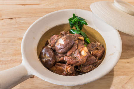 Roasted Pork Spare Ribs and Shiitake mushroom in oyster sauce in a Clay pot on wood table background for ready to serve. Stock Photo