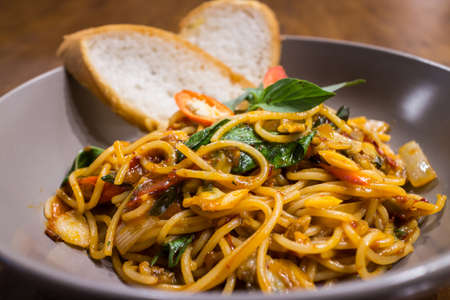 Healthy Very hot and spicy spaghetti Thai Style (Spaghetti Pad Kee Mao) with sweet basil & garlic bread in a gray dish on wood table background for ready to serve. Stock Photo