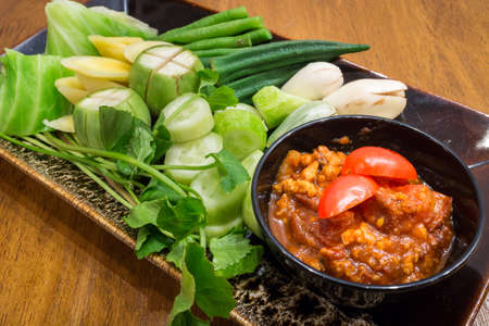 Thai Northern food Style Pork and Tomato Chili Relish (Nam prik ong bruschetta) and tomato spicy dip with pork, serve with vegetables in a black dish on wood table background for ready to serve.