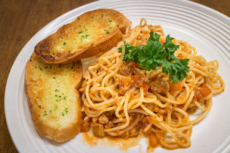 Healthy Spaghetti bolognese with garlic bread in a white dish on wood table background for ready to serve.
