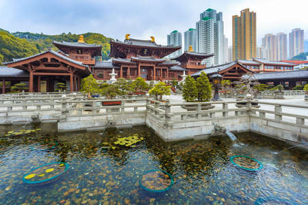 Mahavira Hall in Chi Lin Nunnery, a large Buddhist temple complex built without a single nail, in Diamond Hill with modern buildings in the background, Kowloon, Hong Kong Stock Photo