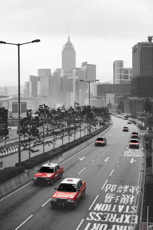 Scenic aerial view of cityscape of landmark buildings along the Lung Wo Road, a road between Central and Wan Chai district, black & white tone with many red cab(Taxi) in Hong Kong island