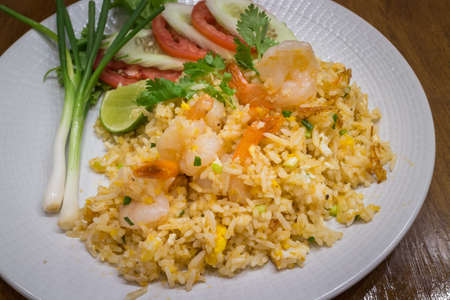 Healthy prawn or shrimp fried rice in a white dish on wood table background for ready to serve.