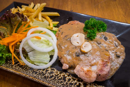 Healthy pork steak with mushroom sauce & salad in a black dish on wood table background for ready to serve.