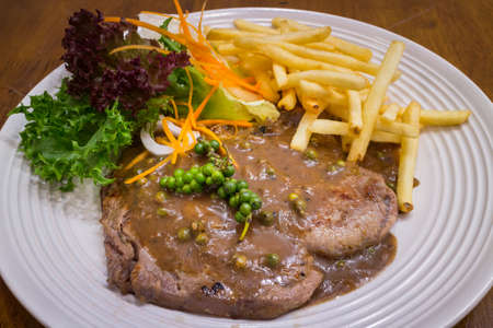 Healthy Beef steak with black pepper sauce & salad in a white dish on wood table background for ready to serve.