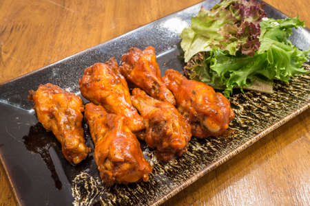 Healthy barbecue chicken wings with salad in a black dish on wood table background for ready to serve.