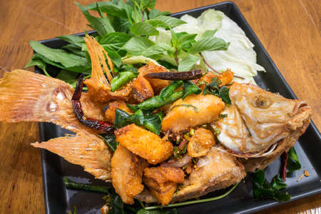Healthy Thai crispy fired fish with salad in a black dish on wood table background for ready to serve.