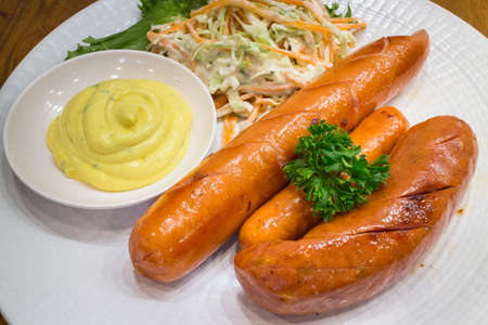 Healthy Three fried sausages with salad in a white dish on wood table background for ready to serve.